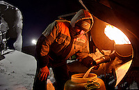 A man working for the oil and gas prospecting company Bashneft collects hot water from a diesel tank at their isolated camp in the Russian Artic. /Felix Features