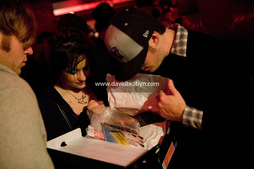 A buyer shows his purchase to friends during Dunkxchange, a market held in a club in New York City, USA, where sneaker collectors trade and sell their rare shoes, 7 January 2007.<br />