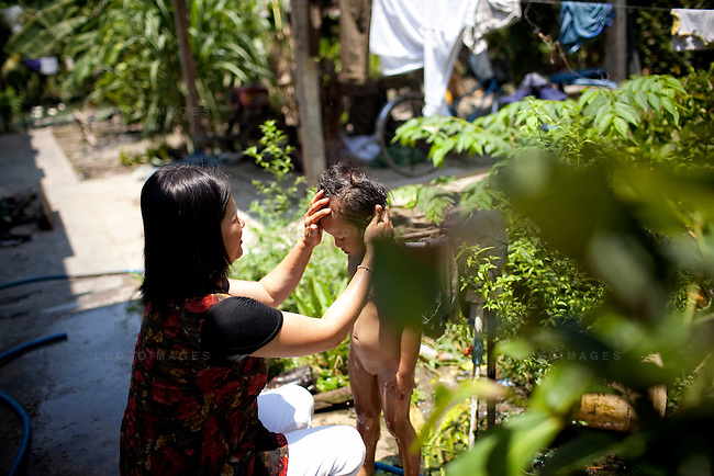 Hien, 4, bathes in clean water with the help of Truong Thi Hang, 37, owner of the Tien Phat enterprise in the Luong Hoa Lac commune.