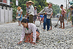 A woman levels rocks by hand as workers pave a street in Kalay, a town in Myanmar. The woman is wearing thanaka, a cosmetic paste, on her face.