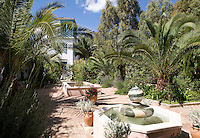 Large palms punctuate the abundant borders of the courtyard