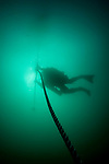 A silhouette of a diver decompressing on a shot line following a deep trimix dive.