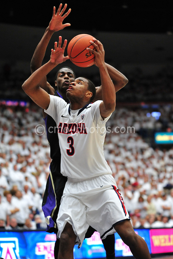 Feb 19, 2011; Tucson, AZ, USA; Arizona Wildcats forward Kevin Parrom (3) draws contact from Washington Huskies forward Justin Holiday (22) in the 1st half of a game at the McKale Center.