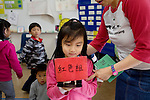 Koey Chan, 5, holds a sign that reads red, in Chinese, as kindergarten teacher, WInsome So, escorts her to her workstation in class, in San Francisco, Ca., on Friday, Sept. 11, 2009. West Portal Elementary School celebrates the 25th anniversary of their Chinese immersion program, the first one in the U.S., Since then, many Chinese programs have opened in the city and the country.
