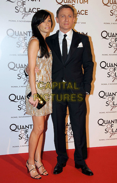"SATSUKI MITCHELL & DANIEL CRAIG.""Quantum of Solace"" Rome Premiere held at the Warner Village Moderno Cinema, Rome Italy..November 5th, 2008.full length black suit beige dress couple clutch bag silver beads beaded .CAP/ADM/Liverani/MB.©Massimo Bruni/Liverani/AdMedia/Capital Pictures"