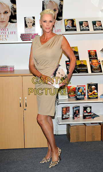 BRIGITTE NIELSEN.Brigitte Nielsen launches her new book 'You Only Get One Life' at the London Book Fair, Earls Court, London, England..April 11th, 2011 .full length sleeveless dress beige leopard print shoes.CAP/CJ.©Chris Joseph/Capital Pictures.