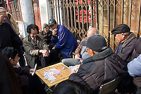 People playing cards on a Xiangqi (the chinese chess) board game in a street..Shanghai, February 2006.