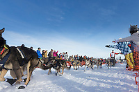 Linwood Fiedler gives high-fives to spectators as he runs down the chute leaving the restart of the Iditarod sled dog race at Willow, Alaska Sunday, March 3, 2013.
