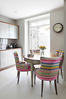 A white kitchen with four chairs upholstered in colourful candy stripe fabric are placed around a Georgian table, which contrasts with the neutral modern units.
