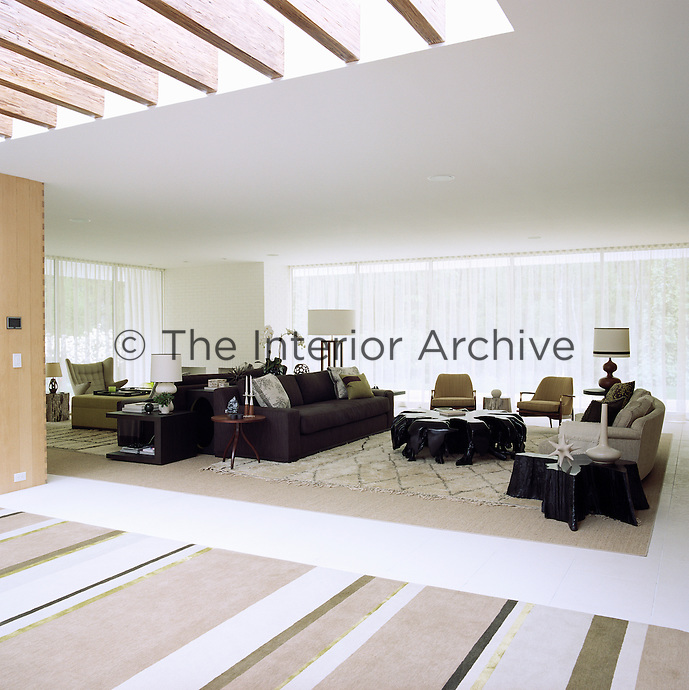 The spacious and airy living room has a dual aspect over the gardens and the central swimming pool and is furnished with an array of mid-century furniture