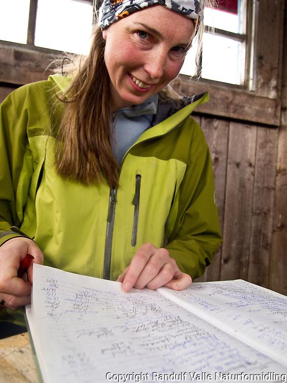 Dame skriver i hytteboka på Svartfjellhytta på Kvaløya i Hammerfest kommune. ---- Svartfjellhytta. Hut on Kvaløya.