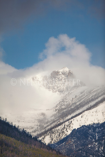 low clouds cling to the snow capped peaks of the bitterroot mountains in western montana