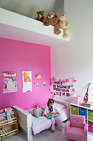 The little girl of the house photographed in her pretty pink and white bedroom in which the furniture, such as the bed and armchair, is on a child's scale