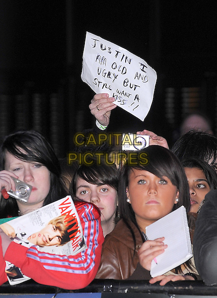 FANS.The UK Premiere of Justin Bieber: Never Say Never, Cineworld, 02 Arena, London, England..February 16th, 2011.half length audience black camera vanity fair i am old and ugly but still want a kiss sign poster .CAP/BEL.©Tom Belcher/Capital Pictures.