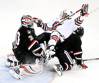 UNO's Brock Montpetit sides off the back of St. Cloud State's Nick Jensen and into goalie Mike Lee during the second period. UNO beat St. Cloud State 3-0 Friday night at Qwest Center Omaha.  (Photo by Michelle Bishop)