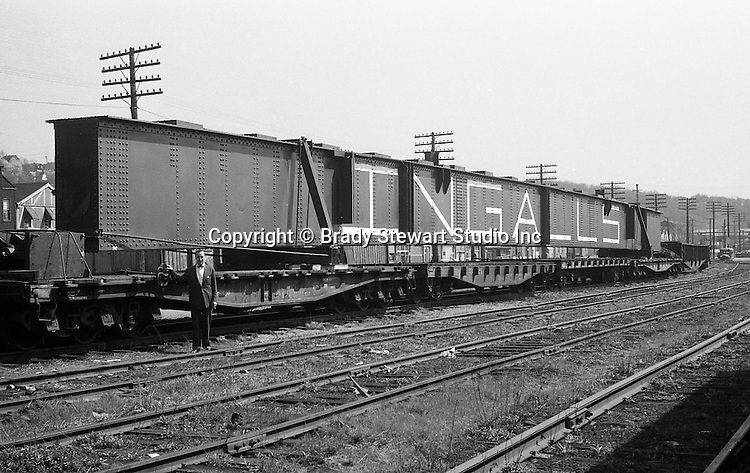 Client: Pennsylvania Railroad<br /> Ad Agency:<br /> Product: Ingalls Steel Products<br /> Location: Oakmont PA <br /> <br /> View of an Ingalls Steel girder being transported by the Pennsylvania Railroad at the Oakmont Station.  The structual beam was fabricated the Ingalls Iron Works for use in highway construction.<br /> Brady Stewart Sr. always recommended using people in location photography assignments like this one to give a sense of relative size.