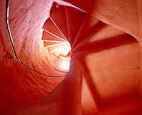 View looking up a spiral staircase in one of the towers which has been painted a dramatic coral pink