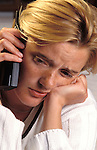 Young woman looking miserable during an unhappy telephone conversation