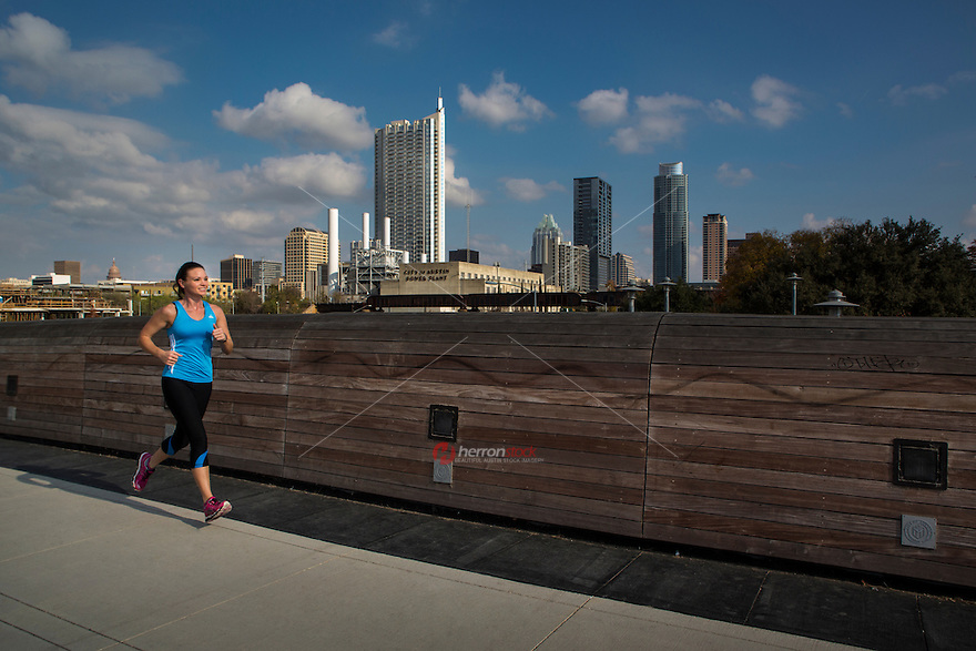 Beautiful and Fit Model Running on Lamar Pedestrian Bridge in Front of the Austin, Texas Skyline during summer time.