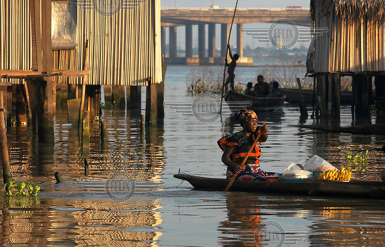 A woman paddles her canoe carrying bananas past houses built on stilts above the water.