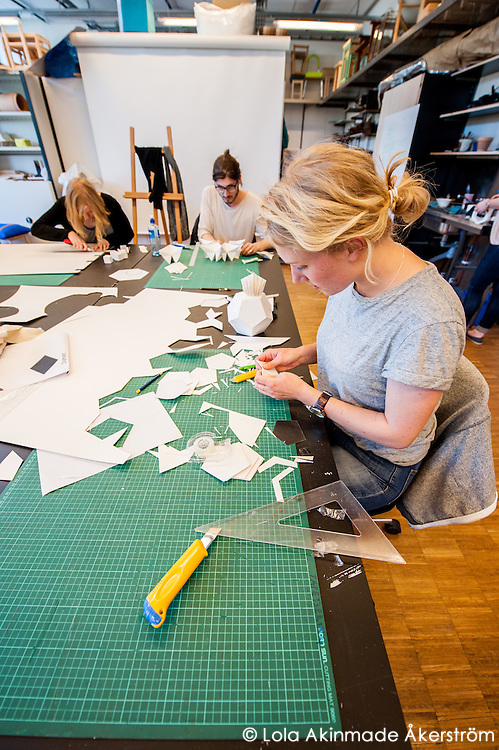 Final-year furniture design students working with paper, sketching pieces and building models.