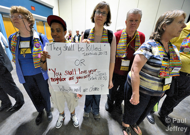 Demonstrators hold a silent vigil as delegates to the 2012 United Methodist General Conference exit a plenary session in Tampa, Florida. The demonstrators are protesting the church's exclusion of gays and lesbians from full inclusion in the life and leadership of the church.