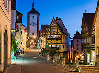 "Germany, Bavaria, Middle Franconia, Rothenburg ob der Tauber: The Ploenlein (""Little Square"") at dusk, road junction with half-timbered houses, view at Siebers Gate (left) and Kobolzeller Gate (right) 