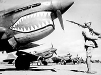 """A Chinese soldier guards a line of American P-40 fighter planes, painted with the shark-face emblem of the `Flying Tigers,' at a flying field somewhere in China."" Ca. 1942."