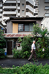 Tokyo, June 25 2013 -  Small house in front of an apprtement building in the Nezu area.