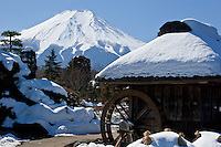 A snow capped Mount Fuji from Iyashi-no-Sato village in Nenba with thatched room cottages called kayabuki. Yamanashi Prefecture. Japan, Wednesday February 13th 2008