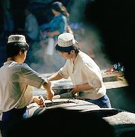 Street vendors preparing food, Silk Route, Turpan, Xinjiang Province, China.