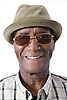 Portrait of an older man wearing a hat and glasses smiling,