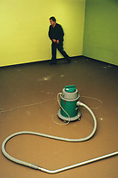 Switzerland. Canton Lucerne. A man is cleaning an empty room with a vacuum cleaner in the Sonnenberg tunnel in Lucerne during the largest civil defense exercise ever held in the country. From 16 to 21 November 1987, almost 1200 men and women converted a motorway tunnel into perhaps the world's largest bunker structure. The civil protectors had to prove during the exercise «Ameise» ( Ants in english) that in an emergency more than 20,000 inhabitants of the city of Lucerne could survive here in the mountain for two weeks. The Sonnenberg Tunnel is a 1,550m  long motorway tunnel, constructed between 1971 and 1976. At its completion it was also the world's largest civilian nuclear fallout shelter, designed to protect 20,000 civilians in the eventuality of war or disaster. Based on a federal law from 1963, Switzerland aims to provide nuclear fallout shelters for the entire population of the country. The construction of a new tunnel near an urban centre was seen as an opportunity to provide shelter space for a large number of people at the same time. The giant bunker was built between 1970 and 1976 at a cost of 40 million Swiss francs. The shelter consisted of the two motorway tunnels (one per direction of travel), each capable of holding 10,000 people in 64 person subdivisions. A seven story cavern between the tunnels contained shelter infrastructure including a command post, an emergency hospital, a radio studio, a telephone centre, prison cells and ventilation machines. The shelter was designed to withstand the blast from a 1 megaton nuclear explosion 1 kilometer away. The blast doors at the tunnel portals are 1.5 meters thick and weigh 350 tons. The logistical problems of maintaining a population of 20,000 in close confines were not thoroughly explored, and testing the installation was difficult because it required closing the motorway and rerouting the usual traffic. The only large-scale test, a five-day exercise in 1987 to practice converting the road tunnels i