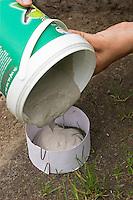 Kinder gießen Tierspur aus Gips, Junge gießt Gips in den Ring aus Karton über dem Trittsiegel, der Fußspur von einem Reh