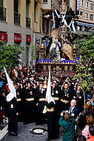 The large throne, with the Paso scene featuring Jesus Christ and Virgin Mary on the top, is carried in a narrow street during the Holy Week celebration in Malaga, Spain, 7 April 2007.