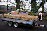 © Joel Goodman - 07973 332324 . 6 December 2013 . Marple , UK . The coffin arrives at Mellor Parish Church , greeted by Vicar Rev. Alex Sanders . The funeral of farmer Bob Watson . His son David Watson drives his father's coffin on a trailer hooked to the back of Bob's favourite tractor through Marple via Bob's local pub before taking it on to the church . Photo credit : Joel Goodman