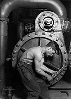 """Records of the Work Progress Administration. <br /> Lewis Hine's 1920 Power house mechanic working on steam pump, one of his """"work portraits"""", shows a working class American in an industrial setting. The carefully posed subject, a young man with wrench in hand, is hunched over, surrounded by the machinery that defines his job. But while constrained by the machinery (almost a metal womb), the man is straining against it—muscles taut, with a determined look—in an iconic representation of masculinity."""