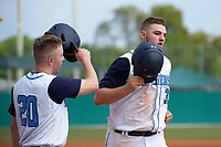 Lasell Lasers Tyler Flaherty (20) congratulates Dom Mascolo (33) after hitting a home run during the first game of a doubleheader against the Edgewood Eagles on March 14, 2016 at Terry Park in Fort Myers, Florida.  Edgewood defeated Lasell 9-7.  (Mike Janes/Four Seam Images)