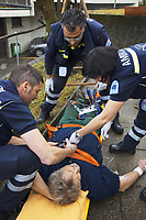 Switzerland. Canton Ticino. Comano. Paramedics team take care of an injured man during an emergency medical intervention. The man was cutting branches off a tree, fell on the ground and broke his right leg. He will be brought to hospital for medical surgery and recovery. Three paramedics wear blue uniforms and work for the Croce Verde Lugano. Both men are professional certified nurses, the woman (R) is a volunteer specifically trained in emergency rescue. The Croce Verde Lugano is a private organization which ensure health safety by addressing different emergencies services and rescue services. Volunteering is generally considered an altruistic activity where an individual provides services for no financial or social gain to benefit another person, group or organization. Volunteering is also renowned for skill development and is often intended to promote goodness or to improve human quality of life. 27.01.2018 © 2018 Didier Ruef