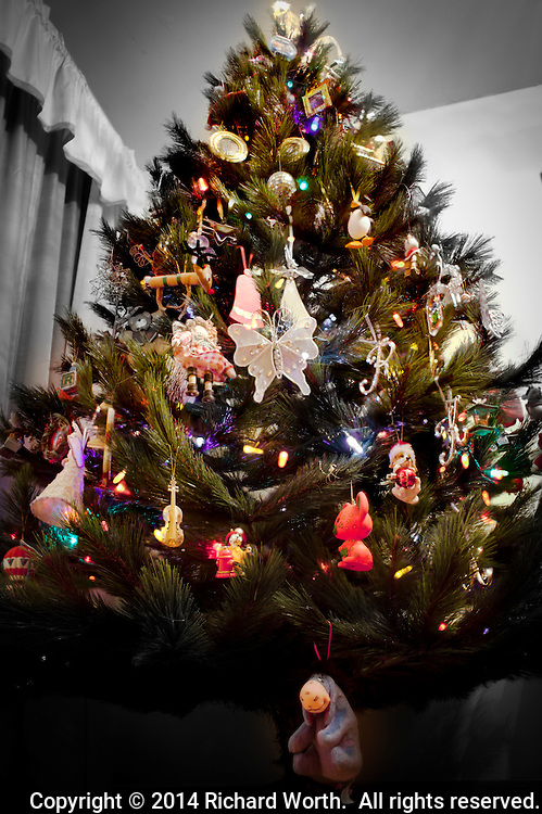 A Christmas tree decorated with colorful ornaments and bight colorful lights against a black and white background.