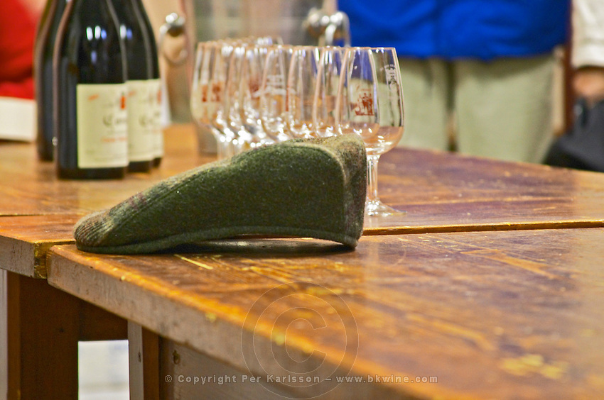 The emblematic cap of Alain Voge on a wooden table and some wine glasses and bottles of Cornas. Alain Voge, Cornas, Ardeche, Ardèche, France, Europe