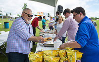 NWA Democrat-Gazette/BEN GOFF @NWABENGOFF<br /> Raul Ruiz (left) of Lowell fills his plate as Jesse Cordova with Visit Rogers serves Friday, June 7, 2019, during the Rogers-Lowell Area Chamber of Commerce annual picnic at Ward Nail Park in Lowell. The park plays host to Lowell's annual Mudtown Days opening Friday evening and continuing from 10:30 a.m. to 10:00 p.m. Saturday with a wide variety of concerts and family activities.