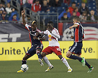 New England Revolution forward Dimitry Imbongo (92) attempts to control the ball as New York Red Bull midfielder Lloyd Sam (10) pressures. In a Major League Soccer (MLS) match, the New England Revolution (blue) tied New York Red Bulls (white), 1-1, at Gillette Stadium on May 11, 2013.