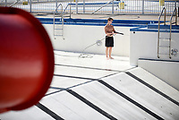 Benji Baugh, assistant manager Springdale Aquatics Center, uses a power washer to clean the sides and bottom of the pool Monday, May 18, 2020, at the center in Springdale. The city has announced Monday, June 8, as the opening date for this year. Check out nwaonline.com/200519Daily/ and nwadg.com/photos for a photo gallery.<br /> (NWA Democrat-Gazette/David Gottschalk)