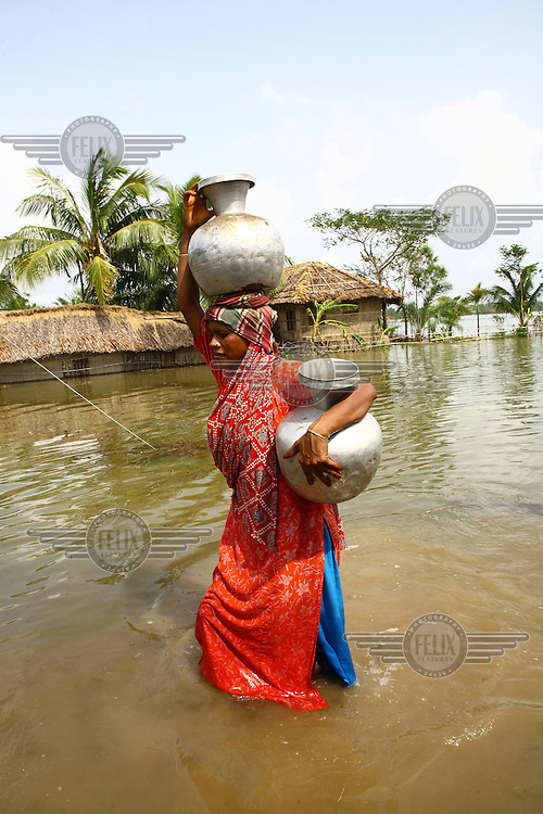 A woman carries water jugs through the floodwaters. There are severe clean water shortages as floodwater becomes stagnant and polluted, contaminating existing water supplies. Thousands of people were displaced in Shyamnagar Upazila, Satkhira district after Cyclone Aila struck Bangladesh on 25/05/2009, triggering tidal surges and floods..