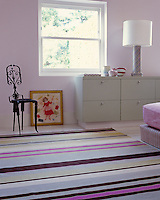 A candy-striped multi-coloured rug adds a feminine touch to this bedroom