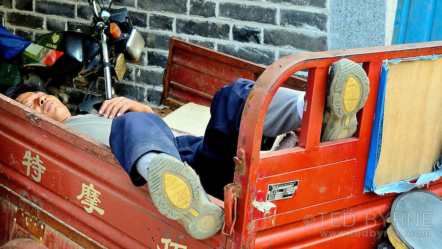 Chinese worker asleep in wagon