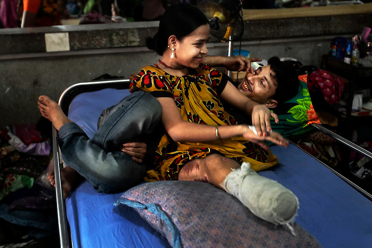 Rana Plaza victim Rebeca, 20, smiles with her husband at a hospital, Rebeca lost her limbs following the building collapse.