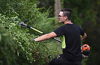 NWA Democrat-Gazette/DAVID GOTTSCHALK Tyler Hunter positions himself before trimming Friday, August 9, 2019, the perimeter bushes at Calvary Baptist Church on No. Porter Road in Fayetteville. Hunter was working with Kendall Prater, with the church, and staff for the job that also included mowing.