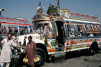 The driver of a typically colourful bus parked in the bus station at Rawalpindi tries to drum up business in a competitive market.